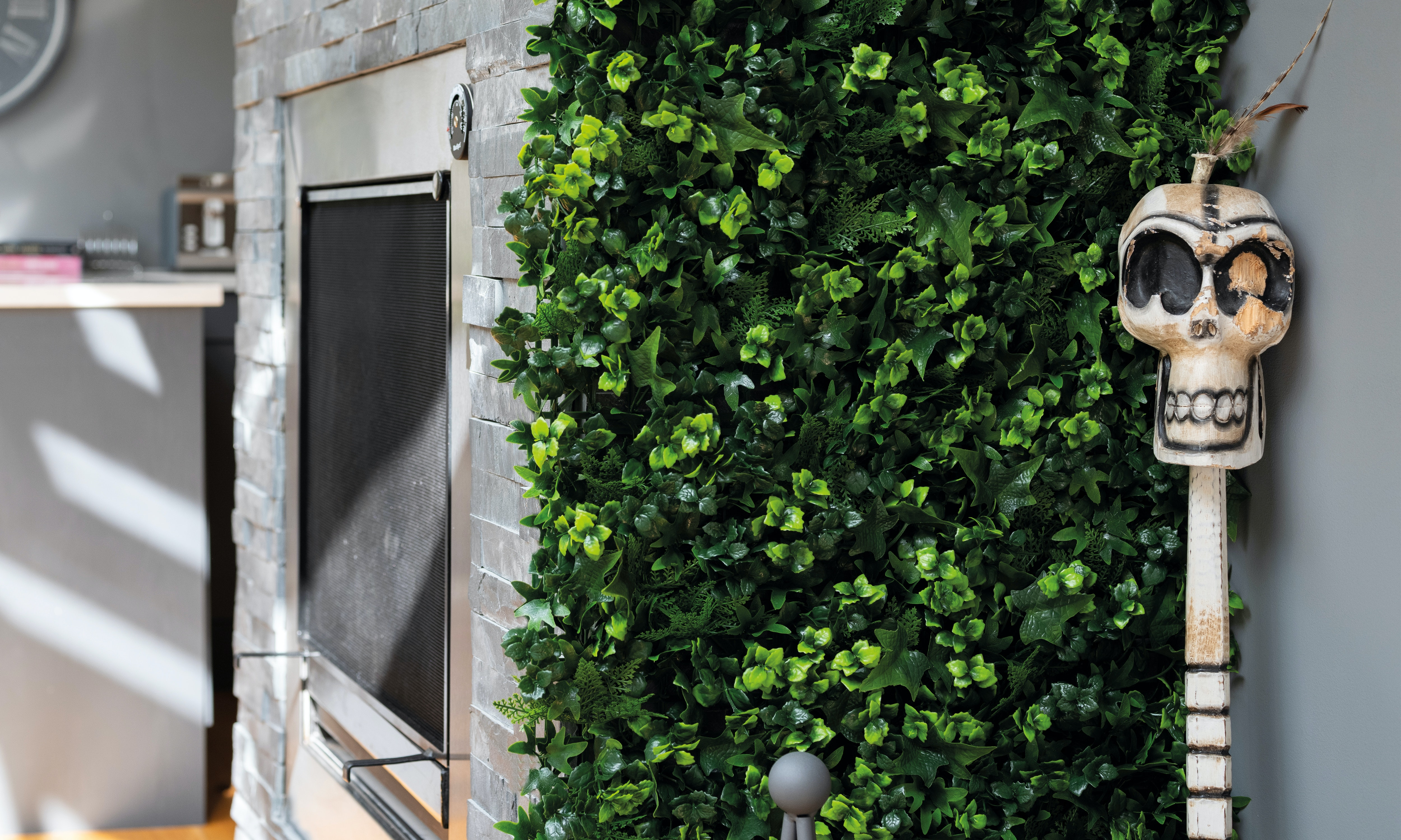 Flame resistant artificial living wall mat by fireplace