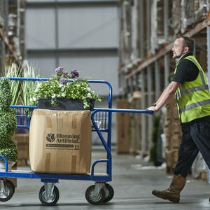 Warehouse operator picking artificial plants Blooming Artificial