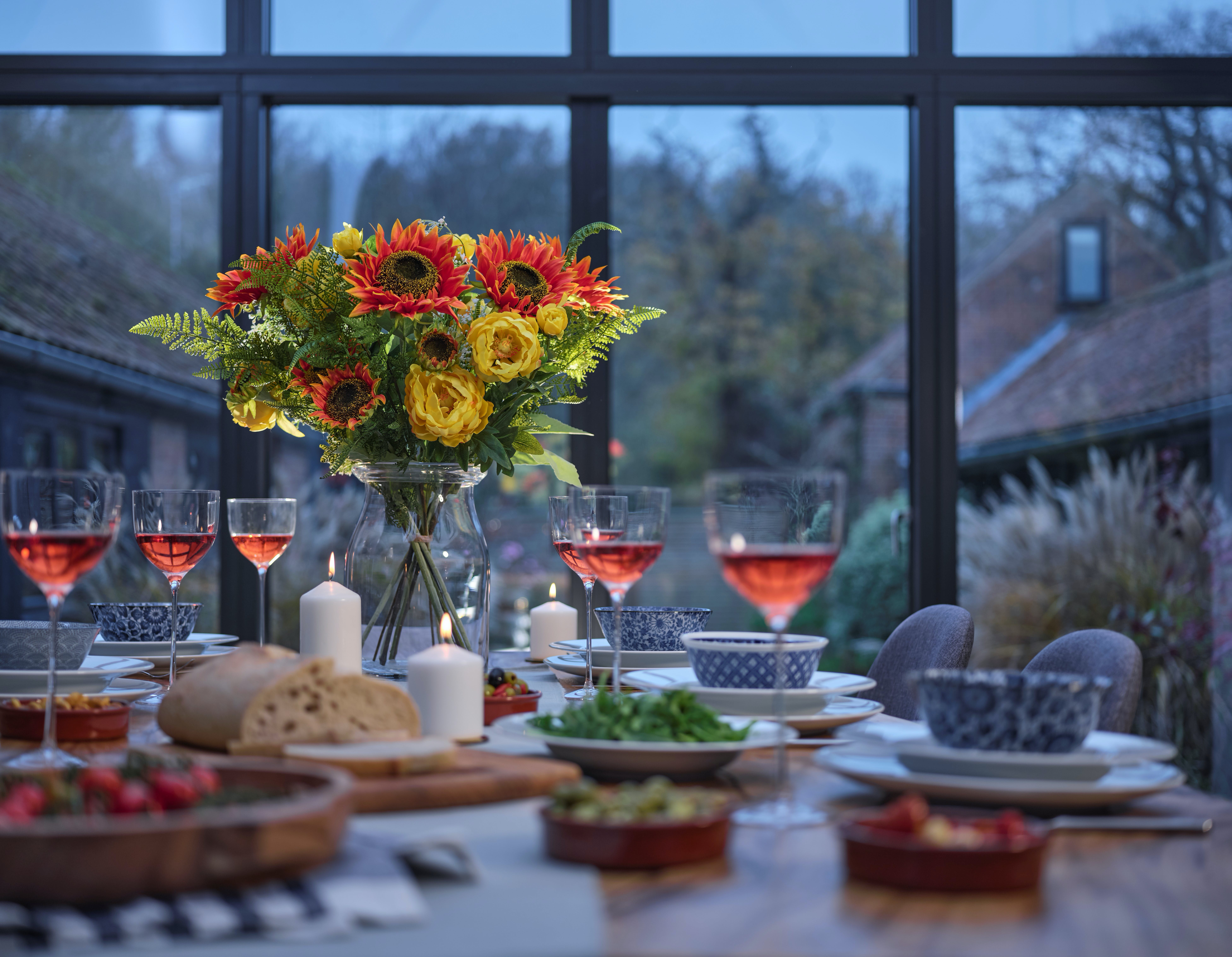 Artificial tequila sunrise flower bouquet on dining table
