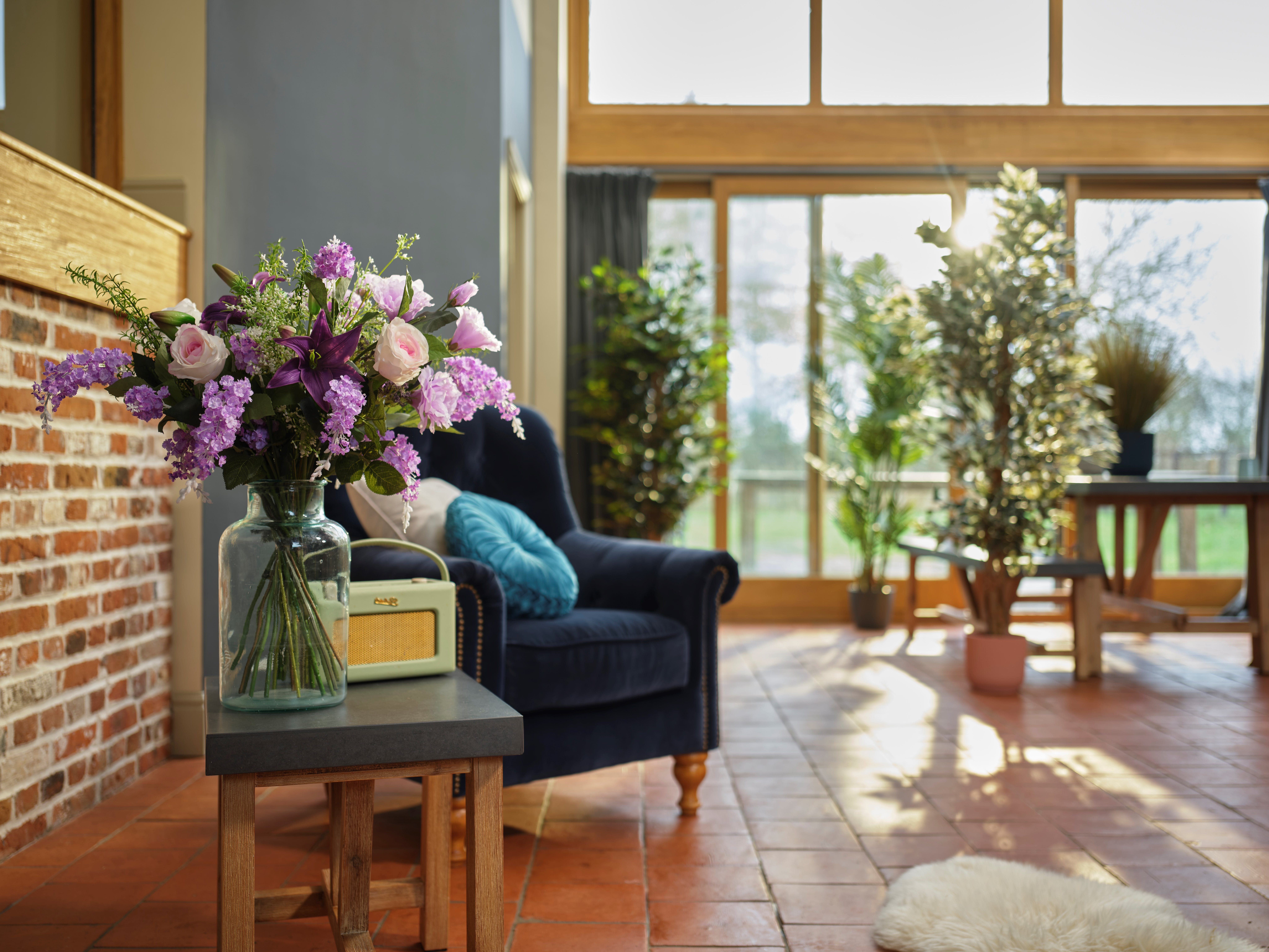 Artificial amethyst bouquet on side table by an armchair