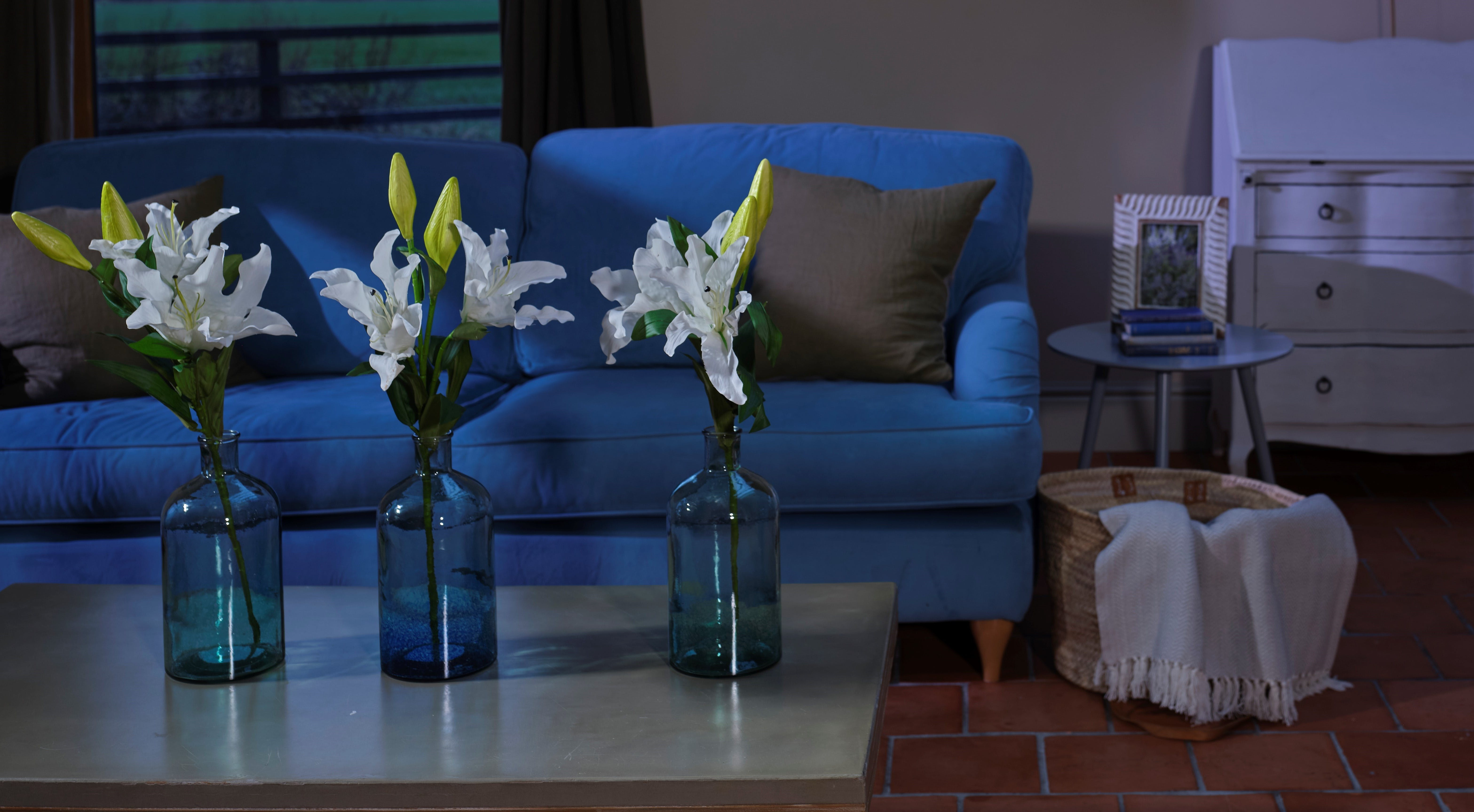 Artificial oriental lily stem in glass vase in living room