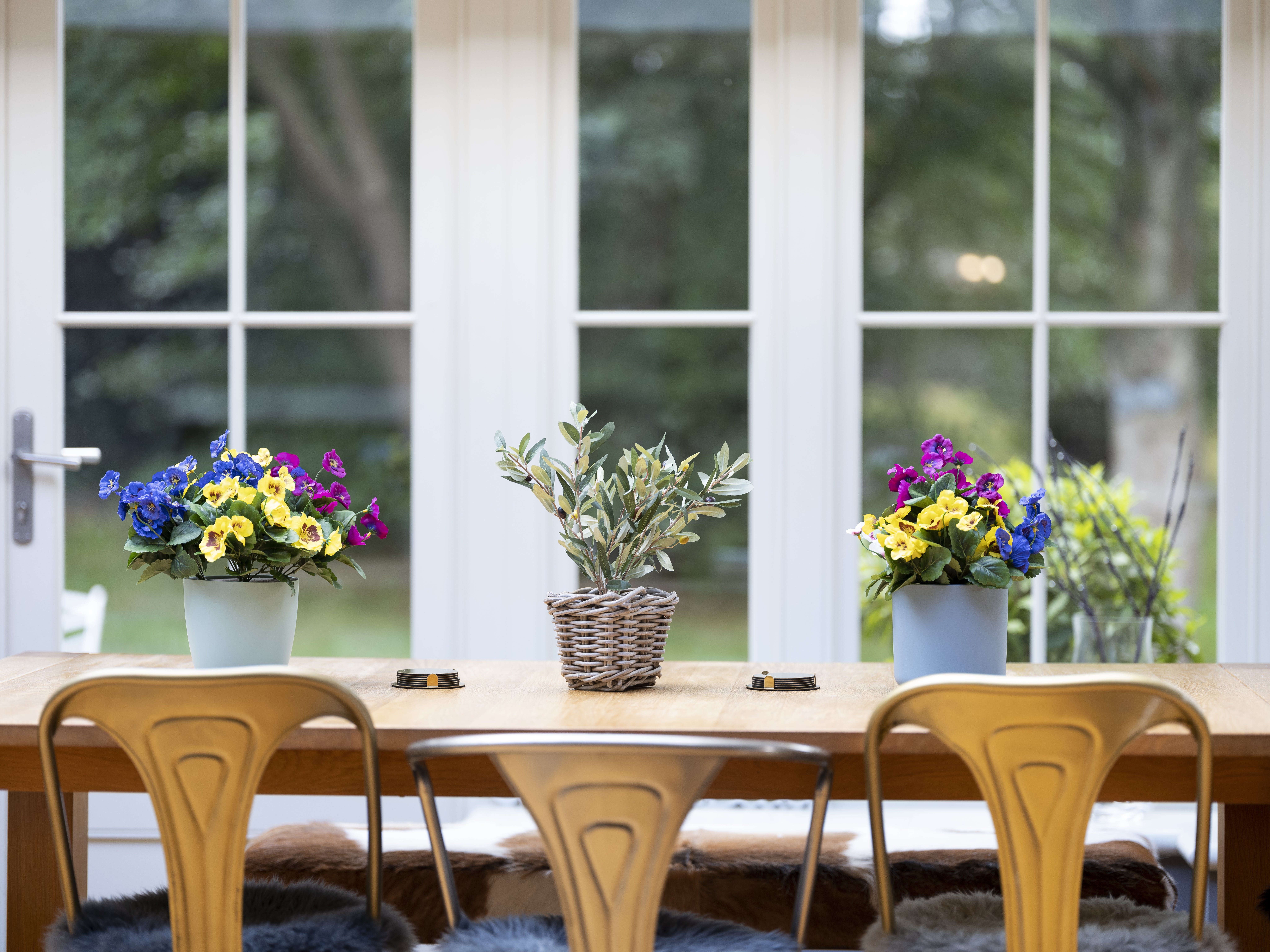 Artificial pansy bush arrangement on dining table