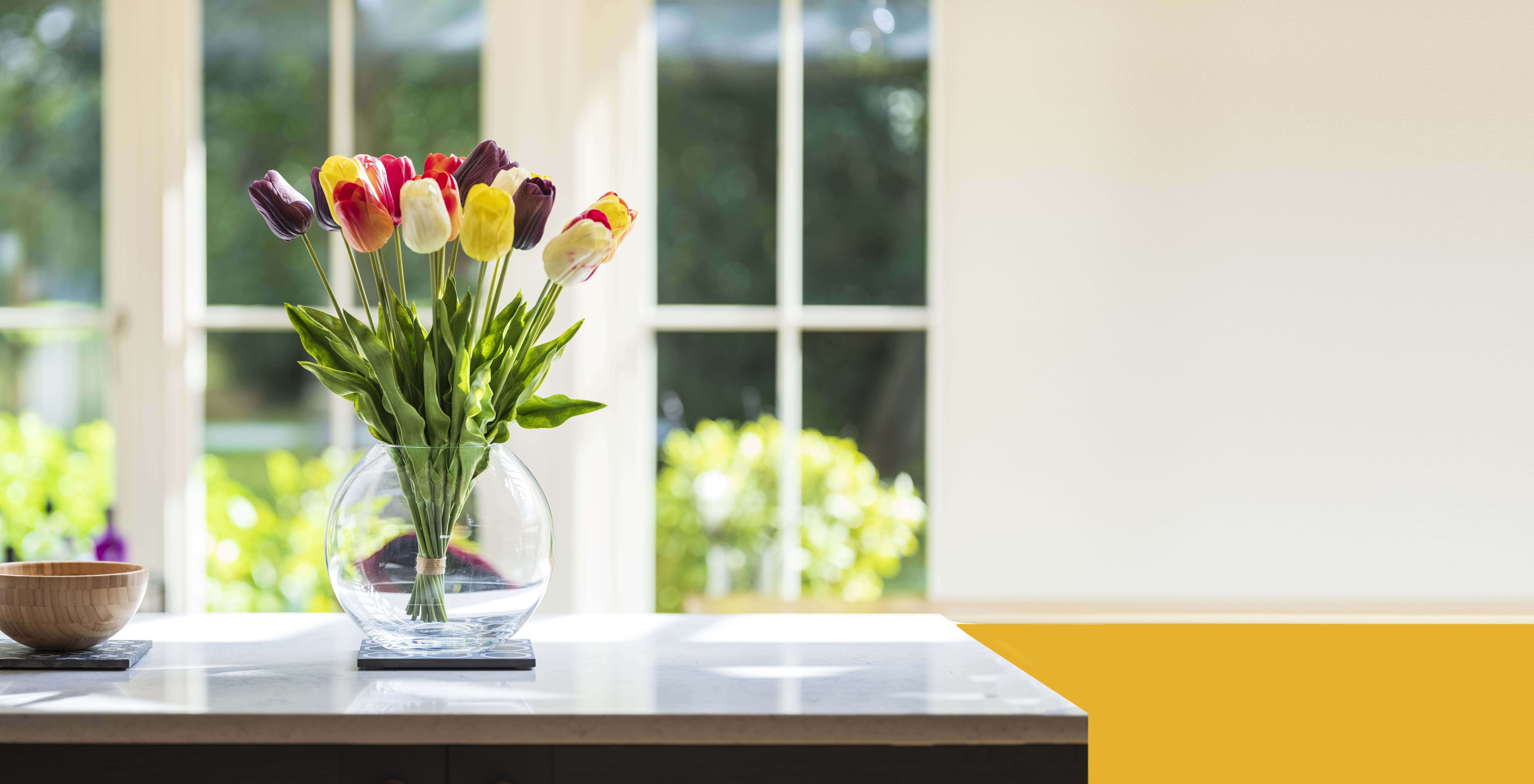 Bunch of artificial tulips on kitchen counter