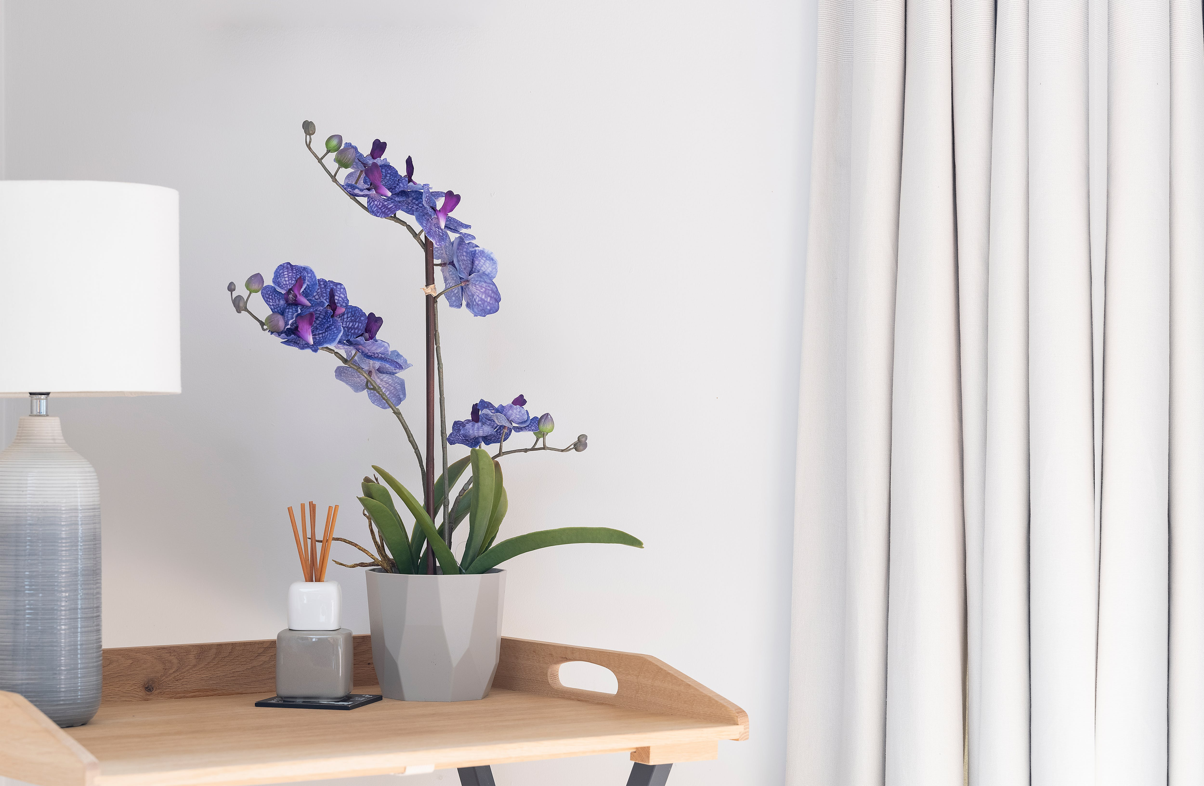 Purple artificial vanda orchid on side table